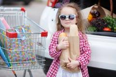 Muchacha con un carro de la compra lleno de ultramarinos cerca del coche Imágenes de archivo libres de regalías