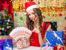 Muchacha con un chèques-cadeaux de la Navidad del fan Foto de archivo libre de regalías
