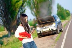 Muchacha con un coche quebrado Imágenes de archivo libres de regalías