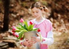 Muchacha con un compartimiento de tulipanes Imagen de archivo libre de regalías