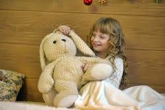 Muchacha con un conejo del juguete Foto de archivo libre de regalías