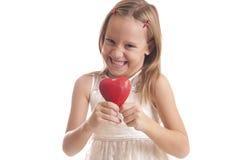 Muchacha con un corazón rojo en un fondo blanco Fotos de archivo libres de regalías