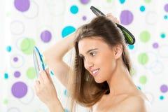 Muchacha con un espejo que se peina el pelo Imágenes de archivo libres de regalías