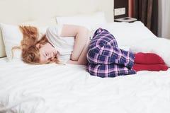 Muchacha con un estómago enfermo en la cama Fotos de archivo libres de regalías