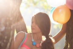 Muchacha con un globo en árbol Imagen de archivo