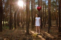 Muchacha con un globo en el corazón del bosque Fotografía de archivo
