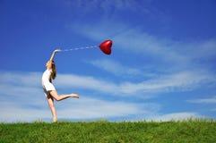 Muchacha con un globo rojo bajo la forma de corazón Imágenes de archivo libres de regalías