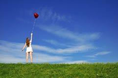 Muchacha con un globo rojo bajo la forma de corazón Fotografía de archivo libre de regalías