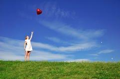 Muchacha con un globo rojo bajo la forma de corazón Foto de archivo libre de regalías