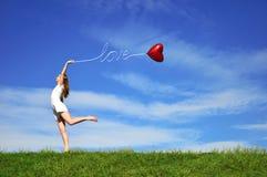 Muchacha con un globo rojo bajo la forma de corazón Imagen de archivo libre de regalías