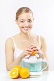 Muchacha con un juicer y las naranjas en un gris Imágenes de archivo libres de regalías