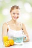 Muchacha con un juicer y un zumo de naranja Foto de archivo