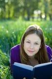 Muchacha con un libro en la hierba Imagen de archivo libre de regalías