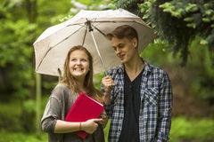 Muchacha con un libro rojo en sus manos y el individuo con el paraguas al aire libre El hablar de los pares Imagen de archivo