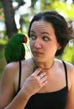 Muchacha con un loro verde Fotografía de archivo