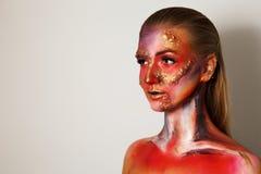 Muchacha con un maquillaje interesante que mira lejos Arte de cuerpo, arte de la cara maquillaje para Halloween, fondo gris Imagenes de archivo