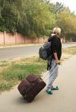 Muchacha con un morral y una maleta Fotografía de archivo