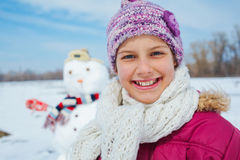 Muchacha con un muñeco de nieve Fotografía de archivo libre de regalías