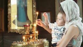 Muchacha con un niño en la luz de la iglesia a la vela almacen de video