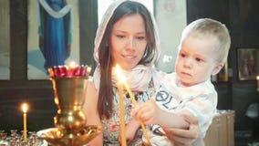Muchacha con un niño en la luz de la iglesia a la vela metrajes
