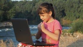 Muchacha con un ordenador portátil cerca de un río Muchacha en la orilla del río con un ordenador portátil Niña con un ordenador  almacen de metraje de vídeo