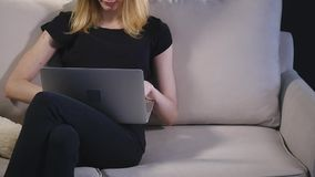 Muchacha con un ordenador portátil en el sofá Fondo negro metrajes