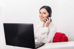 Muchacha con un ordenador portátil en la oficina que llama el teléfono imagenes de archivo