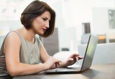 Muchacha con un ordenador portátil en la tabla Imagen de archivo