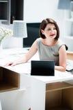 Muchacha con un ordenador portátil en la tabla Imagenes de archivo