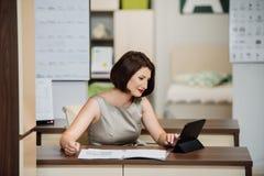 Muchacha con un ordenador portátil en la tabla Imágenes de archivo libres de regalías