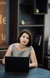 Muchacha con un ordenador portátil en la tabla Foto de archivo libre de regalías
