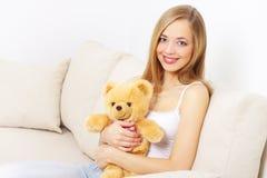 Muchacha con un oso de peluche Imagenes de archivo