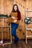 Muchacha con un oso en su mano que se coloca en sitio con la pared de madera Fotografía de archivo