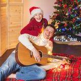 Muchacha con un papá que toca la guitarra y que canta cerca de la Navidad tr Imágenes de archivo libres de regalías