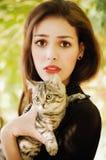 Muchacha con un pequeño gato Fotos de archivo