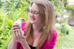 Muchacha con un pequeño pollo Imagen de archivo