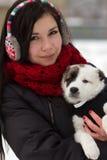 Muchacha con un perrito al aire libre en invierno Foto de archivo