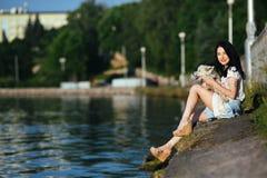 Muchacha con un perro en el lago Fotografía de archivo libre de regalías