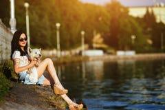 Muchacha con un perro en el lago Imagen de archivo