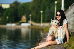 Muchacha con un perro en el lago Imagenes de archivo