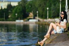 Muchacha con un perro en el lago Fotos de archivo libres de regalías