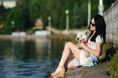 Muchacha con un perro en el lago Imagen de archivo libre de regalías