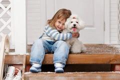 Muchacha con un perro en el pórche de entrada Fotos de archivo libres de regalías