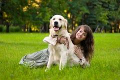 Muchacha con un perro en la hierba Fotos de archivo