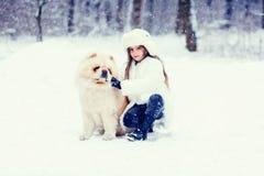 Muchacha con un perro en la madera del invierno Fotografía de archivo
