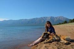 Muchacha con un perro en la orilla del lago Baikal Fotografía de archivo libre de regalías