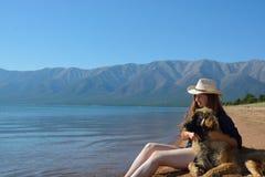 Muchacha con un perro en la orilla del lago Baikal Fotos de archivo