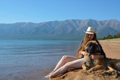 Muchacha con un perro en la orilla del lago Baikal imagenes de archivo
