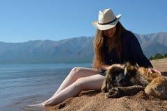 Muchacha con un perro en la orilla del lago Baikal imagen de archivo