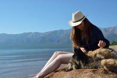 Muchacha con un perro en la orilla del lago Baikal foto de archivo libre de regalías